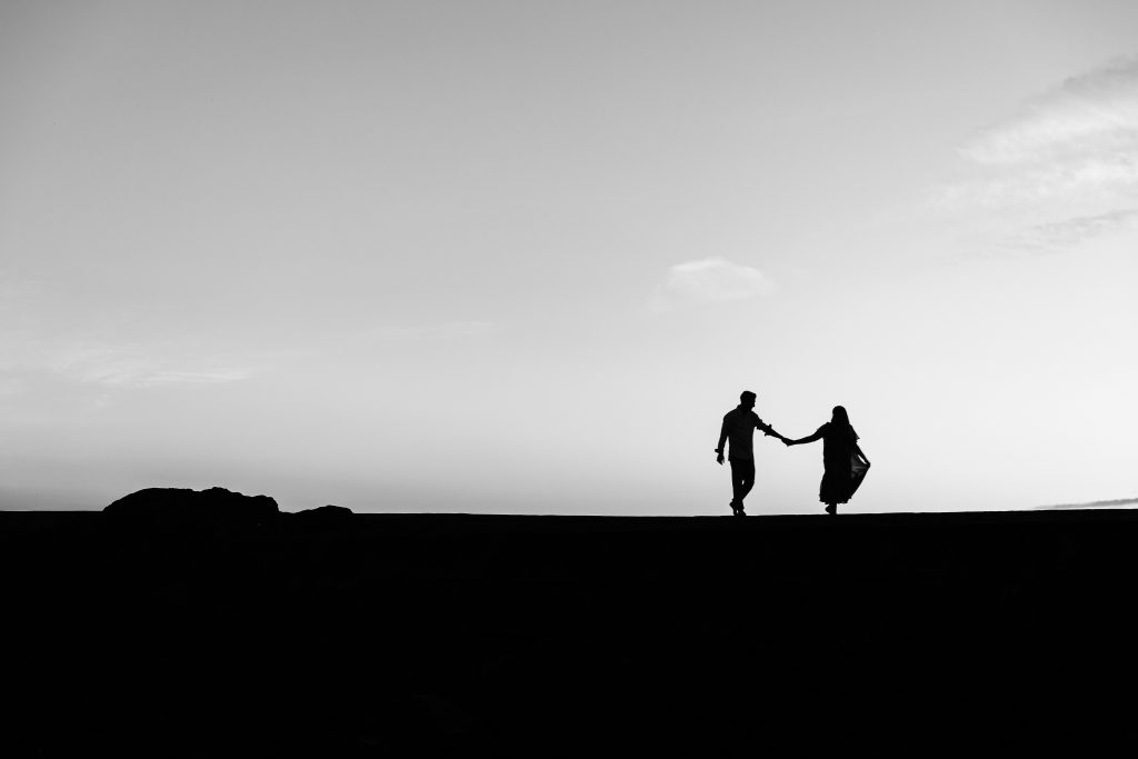silhouette of 2 person standing on the ground